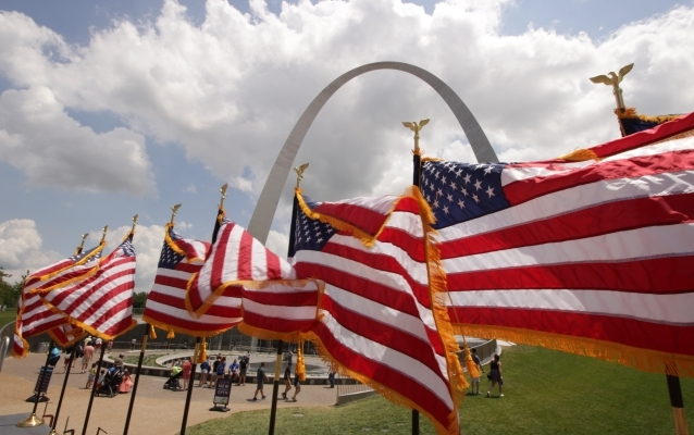 Gateway Arch with American flags in foreground