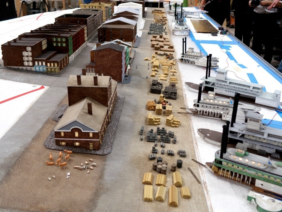 A diorama is under construction depicting buildings, people, livestock, cargo, and steamboats, allowing visitors to experience the historic riverfront era before the Gateway Arch.